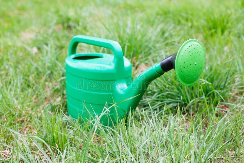 Το νέο πράσινο πότισμα μπορεί στεμένος στη χλόη στοκ φωτογραφία