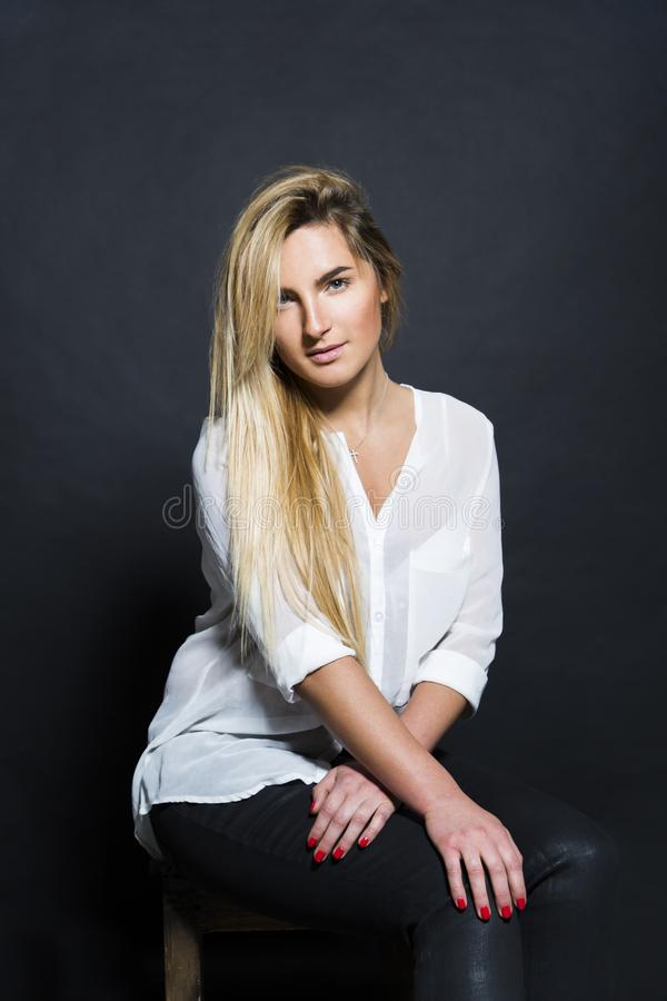 Το νέο προκλητικό ξανθό όμορφο κορίτσι κάθεται στην καρέκλα στοκ φωτογραφία με δικαίωμα ελεύθερης χρήσης