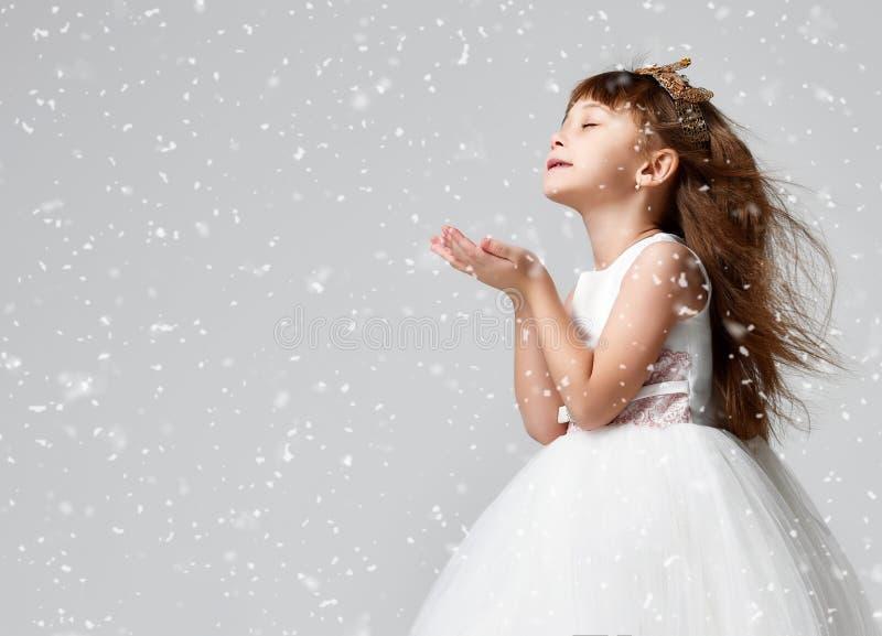 Το νέο πρότυπο μικρών κοριτσιών στο άσπρο χειμερινό φόρεμα κοινωνίας στέκεται στη χρυσή κορώνα με τους ακριβούς πολύτιμους λίθους στοκ εικόνες