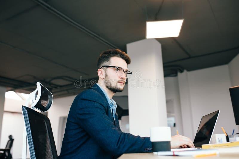 Το νέο σκοτεινός-μαλλιαρό άτομο εργάζεται στον πίνακα στην αρχή Φορά το μπλε πουκάμισο με το μαύρο σακάκι Δακτυλογραφεί στο lap-t στοκ εικόνες με δικαίωμα ελεύθερης χρήσης