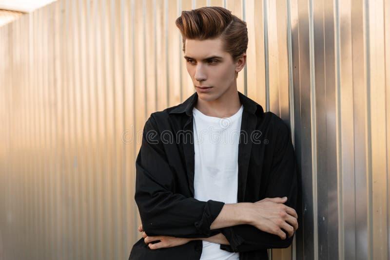 Το νέο σοβαρό άτομο με ένα μοντέρνο hairstyle σε μια μοντέρνη μπλούζα σε ένα εκλεκτής ποιότητας μαύρο πουκάμισο στέκεται κοντά σε στοκ φωτογραφία με δικαίωμα ελεύθερης χρήσης