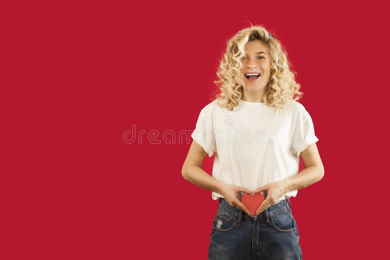 Το νέο συναισθηματικό κορίτσι με μια κόκκινη καρδιά στα χέρια της στέκεται σε ένα απομονωμένο κόκκινο υπόβαθρο Έννοια ημέρας ερασ στοκ εικόνες με δικαίωμα ελεύθερης χρήσης
