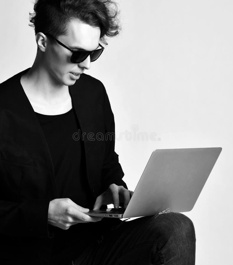 Το νέο σύγχρονο άτομο στο μαύρο κοστούμι σακακιών τζιν και τα γυαλιά ηλίου λειτουργούν στο φορητό προσωπικό υπολογιστή στοκ εικόνες