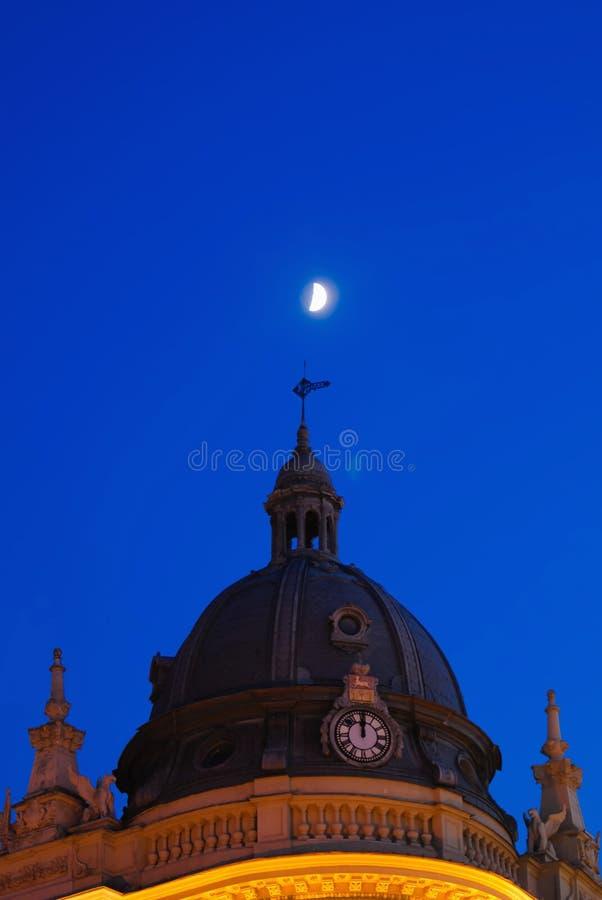 Το νέο φεγγάρι λάμπει πέρα από το θόλο θόλων στον πίνακα ρολογιών βραδιού στοκ εικόνα