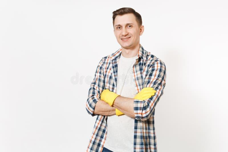 Το νέο χαμογελώντας άτομο που φορά το ελεγμένο πουκάμισο, κίτρινα γάντια που κρατούν τα χέρια δίπλωσε απομονωμένος στο άσπρο υπόβ στοκ εικόνες