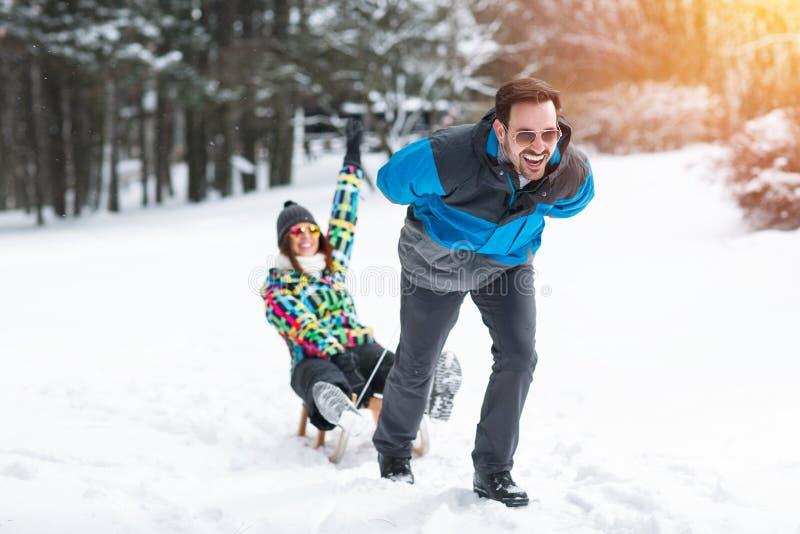 Το νέο χαμογελώντας άτομο τραβά την αγάπη του στο έλκηθρο στο όμορφο βουνό στοκ εικόνες με δικαίωμα ελεύθερης χρήσης