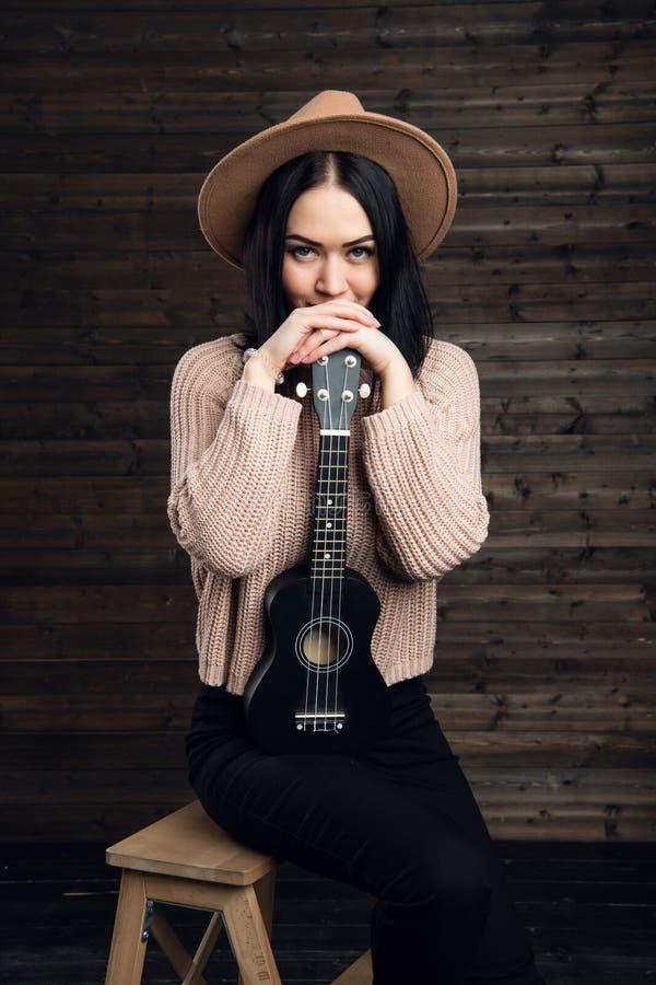 Το νέο χαμογελώντας κορίτσι με ένα ukulele κάθεται στο στούντιο σε ένα ξύλινο υπόβαθρο στοκ φωτογραφίες με δικαίωμα ελεύθερης χρήσης