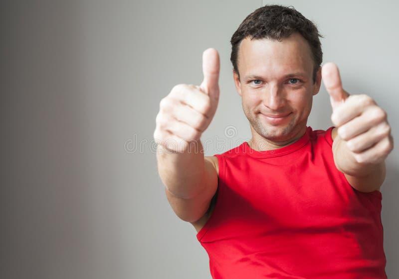 Το νέο χαμογελώντας άτομο παρουσιάζει αντίχειρες στοκ εικόνες