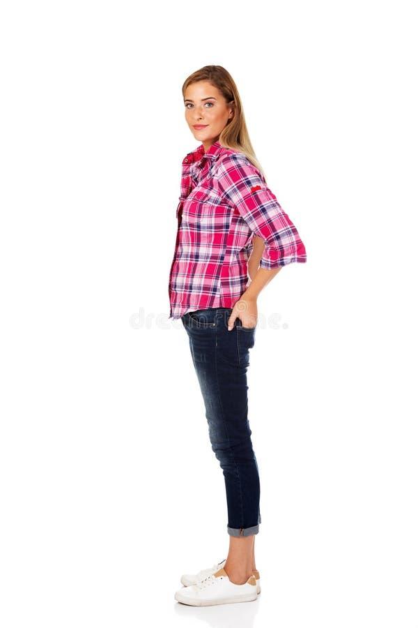 Το νέο χαμογελώντας θηλυκό που στέκεται με παραδίδει την τσέπη στοκ εικόνες