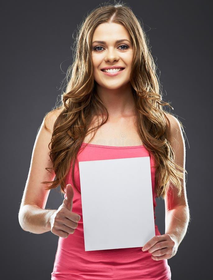 Το νέο χαμόγελο γυναικών, παρουσιάζει αντίχειρα, κρατώντας το λευκό κενό πίνακα στοκ φωτογραφία με δικαίωμα ελεύθερης χρήσης
