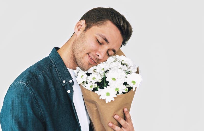 Το νέο όμορφο άτομο με τις ιδιαίτερες προσοχές απολαμβάνει τη μυρωδιά των λουλουδιών Ελκυστικό αρσενικό με μια δέσμη των λουλουδι στοκ φωτογραφία με δικαίωμα ελεύθερης χρήσης