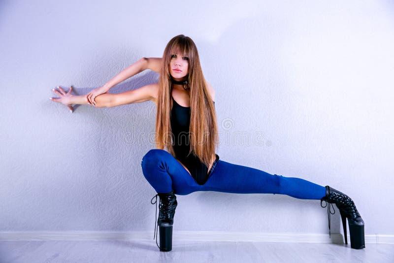 Το νέο όμορφο εύκαμπτο κορίτσι στο μαύρο jumpsuit και τα υψηλά τακούνια θέτει σε ένα στούντιο χορού Πλαίσιο επάνω στη λουρίδα, φό στοκ εικόνα