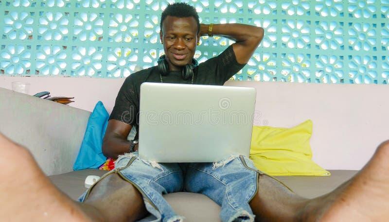 Το νέο όμορφο και ευτυχές αμερικανικό επιχειρησιακό άτομο μαύρων Αφρικανών hipster που λειτουργούν με το φορητό προσωπικό υπολογι στοκ φωτογραφίες