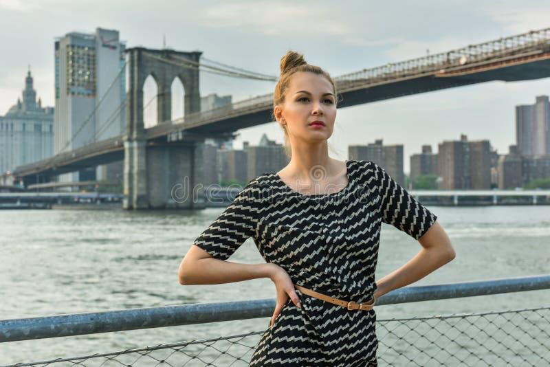 Το νέο όμορφο κορίτσι έντυσε κομψά την τοποθέτηση στην αποβάθρα με τη γέφυρα του Μπρούκλιν στο υπόβαθρο στοκ φωτογραφία με δικαίωμα ελεύθερης χρήσης