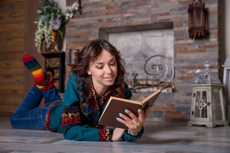 Το νέο όμορφο κορίτσι διαβάζει ένα βιβλίο κοντά σε μια εστία, που τυλίγεται σε ένα θερμό μάλλινο κάλυμμα, κτυπά βίαια Άνετο βράδυ στοκ φωτογραφία