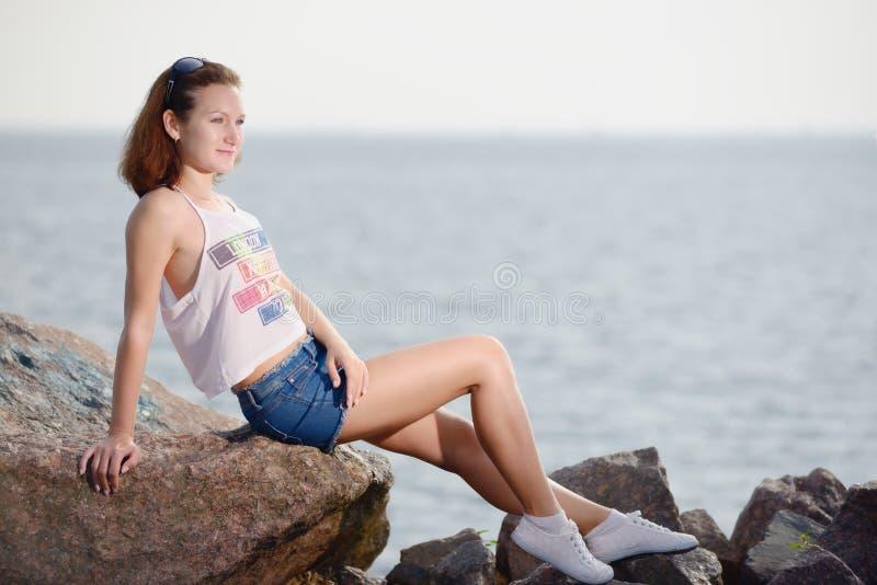 Το νέο όμορφο κορίτσι κάθεται στην πέτρα κοντά στη θάλασσα στοκ φωτογραφία με δικαίωμα ελεύθερης χρήσης