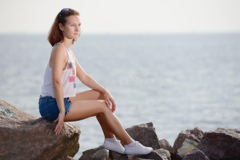 Το νέο όμορφο κορίτσι κάθεται στην πέτρα κοντά στη θάλασσα στοκ φωτογραφία