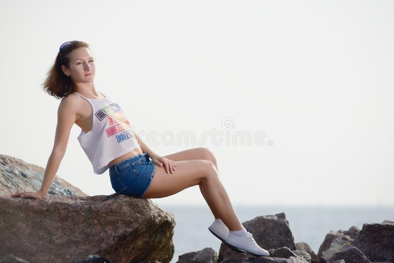 Το νέο όμορφο κορίτσι κάθεται στην πέτρα κοντά στη θάλασσα στοκ εικόνα με δικαίωμα ελεύθερης χρήσης