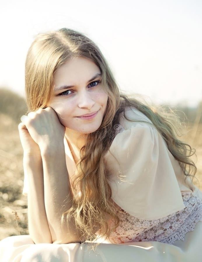 Το νέο όμορφο κορίτσι με μακρυμάλλη που ντύνεται στο ελαφρύ κοντός-sleeved φόρεμα κλίνει το μάγουλό της στην πυγμή της και εξετάζ στοκ φωτογραφίες