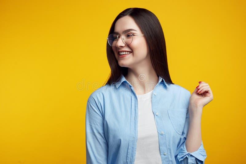 Το νέο όμορφο κορίτσι με eyeglasses, φαίνεται αριστερή πλευρά, σκέφτεται για κάτι, κάνει τα σχέδια στο μυαλό, φορά τα περιστασιακ στοκ φωτογραφίες με δικαίωμα ελεύθερης χρήσης