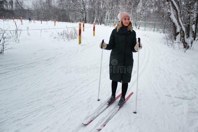 Το νέο όμορφο κορίτσι πηγαίνει στη χειμερινή εποχή σε μια κινηματογράφηση σε πρώτο πλάνο κλίσεων σκι στοκ εικόνες