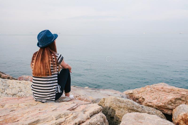 Το νέο όμορφο κορίτσι σε ένα καπέλο κάθεται στους βράχους στην ακτή και εξετάζει την απόσταση Υπόλοιπο, διακοπές, χαλάρωση στοκ εικόνα