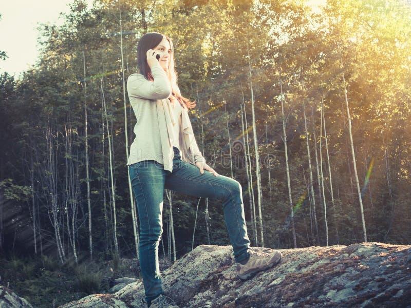 Το νέο όμορφο κορίτσι χαμογελά και μιλά στο τηλέφωνο στεμένος σε μια μεγάλη πέτρα στοκ φωτογραφία
