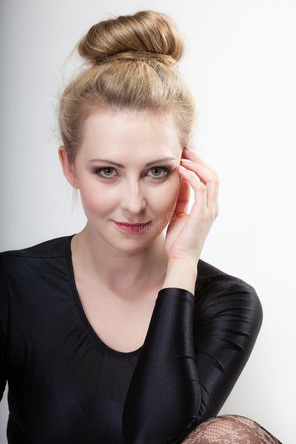 Το νέο όμορφο ξανθό κορίτσι πορτρέτου αποτελεί και κουλούρι τρίχας στοκ φωτογραφία με δικαίωμα ελεύθερης χρήσης