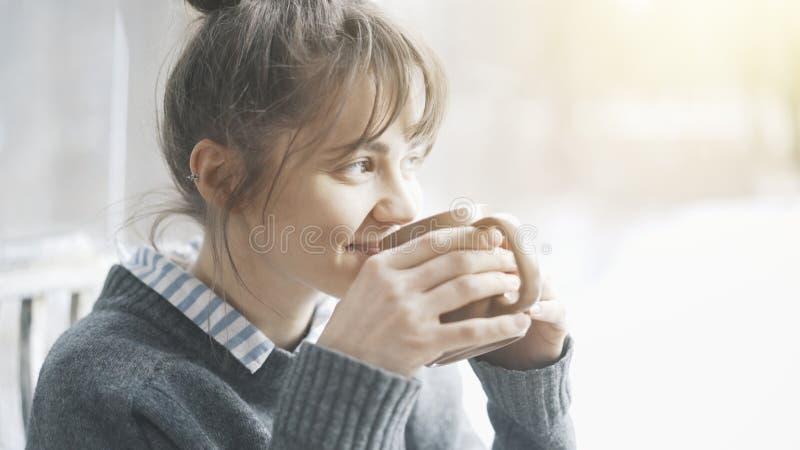 Το νέο όμορφο χαμόγελο γυναικών που φορά ένα γκρίζο πουλόβερ απολαμβάνει το τσάι της σε έναν καφέ και μια αφηρημάδα στοκ φωτογραφία