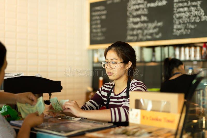 Το νέο barista που παίρνει τα χρήματα από τον πελάτη πληρώνει για το ποτό στη καφετερία στοκ φωτογραφίες με δικαίωμα ελεύθερης χρήσης