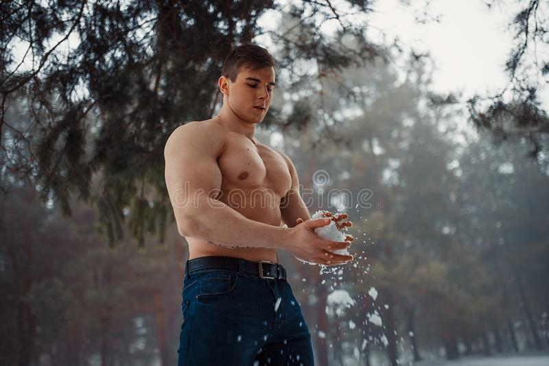 Το νέο bodybuilder με το γυμνό κορμό σκουπίζει το σώμα του από το χιόνι στο δάσος το χειμώνα στοκ εικόνες