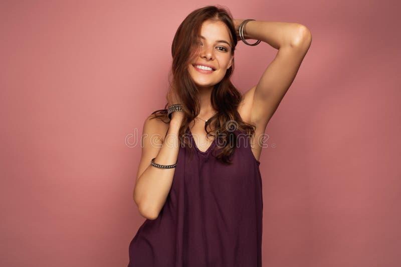 Το νέο brunette αγγίζει τη σγουρή τρίχα της χαμογελώντας στη κάμερα, ρόδινο υπόβαθρο στοκ φωτογραφίες