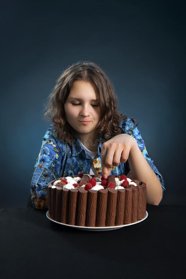 Το νέο brunette σε μια διατροφή παίρνει ήπια το μούρο σμέουρων από ένα κέικ σοκολάτας στοκ φωτογραφία με δικαίωμα ελεύθερης χρήσης