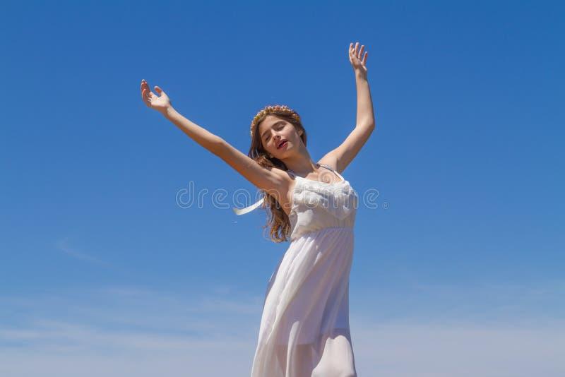 Το νέο brunette στο άσπρο ψιλό φόρεμα απολαμβάνει στοκ εικόνα με δικαίωμα ελεύθερης χρήσης