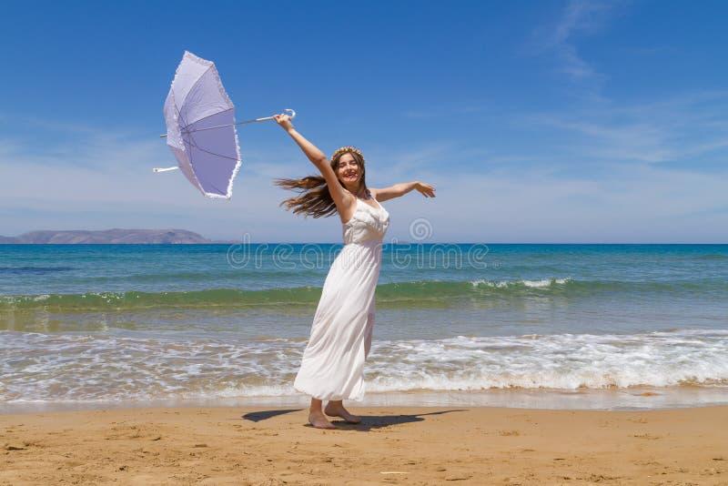 Το νέο brunette στο άσπρο ψιλό φόρεμα απολαμβάνει στοκ φωτογραφία με δικαίωμα ελεύθερης χρήσης