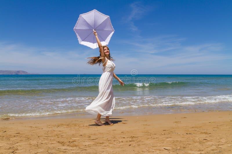Το νέο brunette στο άσπρο ψιλό φόρεμα απολαμβάνει στοκ φωτογραφία