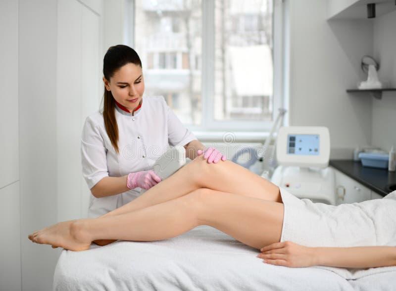Το νέο cosmetician γιατρών εκτελεί μια καλλυντική διαδικασία τα πόδια με την ηλεκτρονική ιατρική συσκευή στο κατάστημα ομορφιάς στοκ φωτογραφίες με δικαίωμα ελεύθερης χρήσης