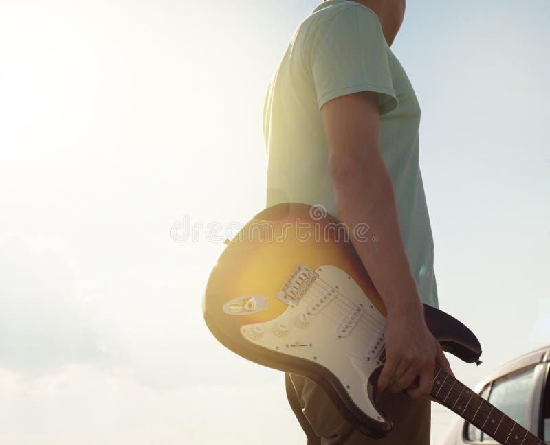 Το νέο hipster σε μια μπλε μπλούζα με μια κιθάρα στέκεται στο δρόμο σε αντίθεση με το φως του ήλιου και το έντονο φως, μια θερινή στοκ φωτογραφία με δικαίωμα ελεύθερης χρήσης