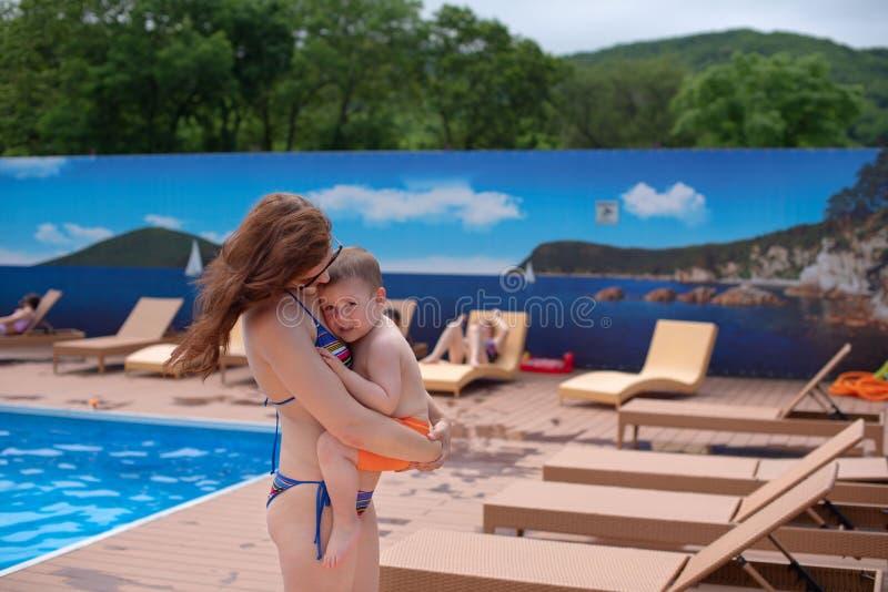 Το νέο mom που κρατά ένα μωρό χαλαρώνοντας από τη λίμνη λάμπει το φωτεινό ταξίδι οικογενειακών διακοπών ήλιων θερινή περίοδο στοκ εικόνα με δικαίωμα ελεύθερης χρήσης