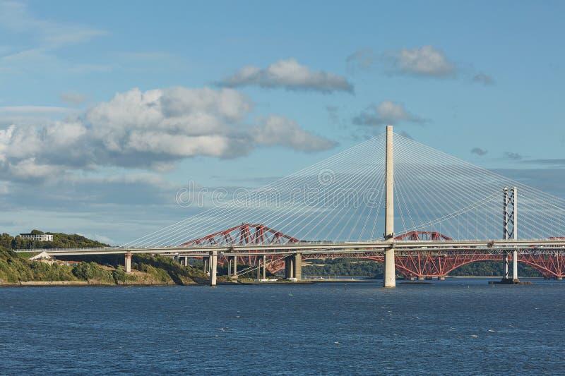 Το νέο Queensferry που διασχίζει τη γέφυρα πέρα από την εκβολή εμπρός με την παλαιότερη εμπρός οδική γέφυρα και την εικονική εμπρ στοκ εικόνα
