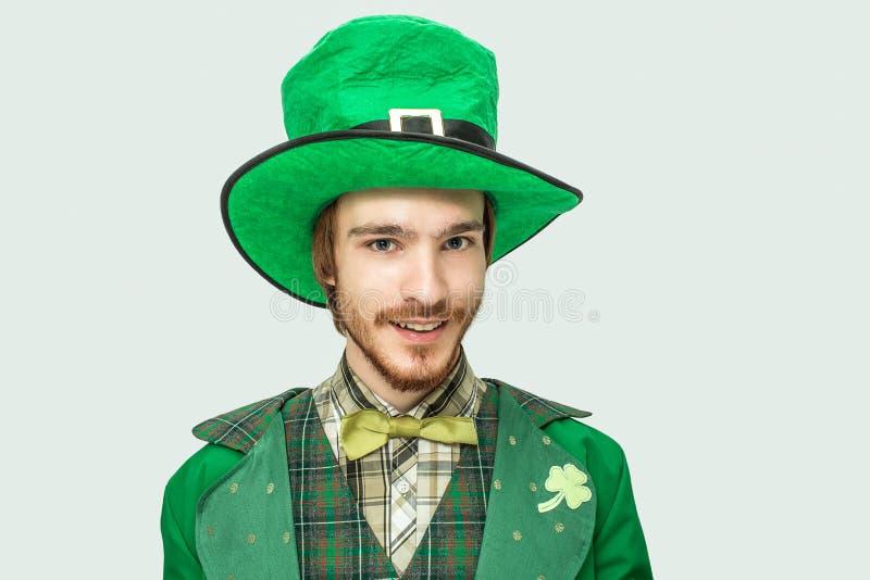 Το νέο redhead άτομο στο πράσινο κοστούμι Αγίου Πάτρικ και το καπέλο φαίνονται κατευθείαν κάμερα Στην άσπρη ανασκόπηση στοκ εικόνα με δικαίωμα ελεύθερης χρήσης