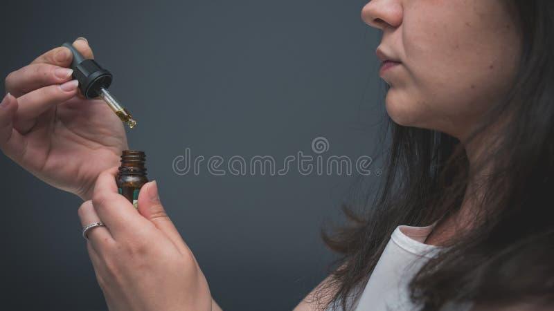 Το νεαρό άτομο χρησιμοποιεί το πετρέλαιο κάνναβης Η κάνναβη είναι μια έννοια της βοτανικής ιατρικής στοκ εικόνες