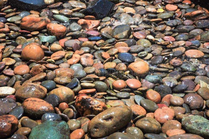 Το νερό είναι πτώση στο ζωηρόχρωμο βράχο στο χρόνο μεσημεριού στοκ εικόνα με δικαίωμα ελεύθερης χρήσης