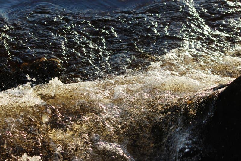Το νερό ποταμού του βόρειου ποταμού Dvina κτυπά ενάντια στην ακτή πετρών στοκ φωτογραφίες