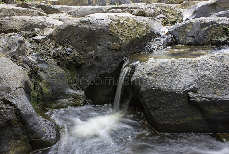 Το νερό που ρέει πέρα από τους βράχους και τα δέντρα κάτω από έναν καταρράκτη στον καταρράκτη Khao Ito, Prachin Buri στην Ταϊλάνδ στοκ εικόνα με δικαίωμα ελεύθερης χρήσης