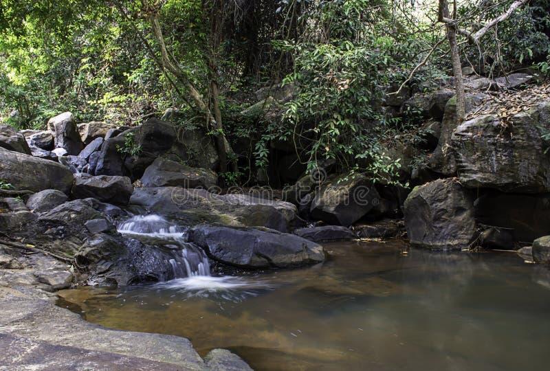 Το νερό που ρέει πέρα από τους βράχους και τα δέντρα κάτω από έναν καταρράκτη στον καταρράκτη Khao Ito, Prachin Buri στην Ταϊλάνδ στοκ εικόνα
