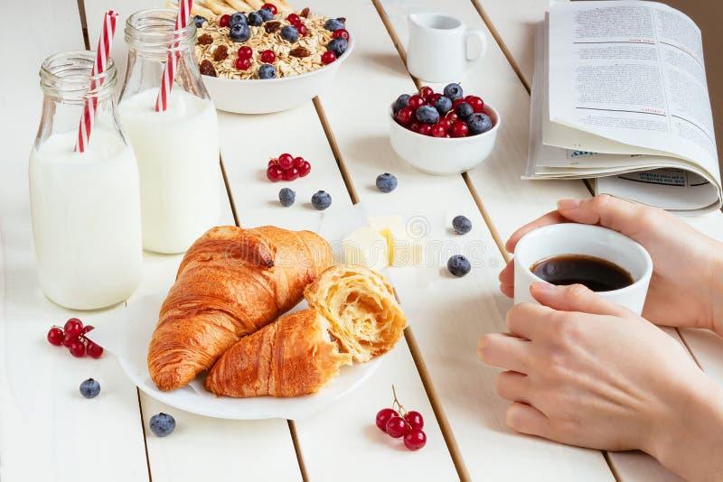 Το νόστιμο πρόγευμα με το φλιτζάνι του καφέ, croissants, βρώμη ξεφλουδίζει, μούρα και γάλα στον άσπρο ξύλινο πίνακα στοκ φωτογραφία