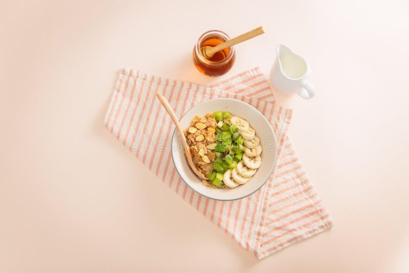 Το νόστιμο υγιές πρόγευμα συστατικών για το μαγείρεμα με το γάλα και τη βρώμη ξεφλουδίζει, μπανάνα, ακτινίδιο στο ρόδινο υπόβαθρο στοκ φωτογραφία με δικαίωμα ελεύθερης χρήσης