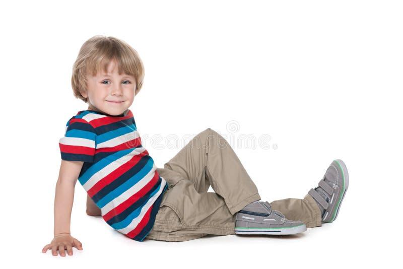 Το ξανθό αγόρι κάθεται στο πάτωμα στοκ φωτογραφία με δικαίωμα ελεύθερης χρήσης