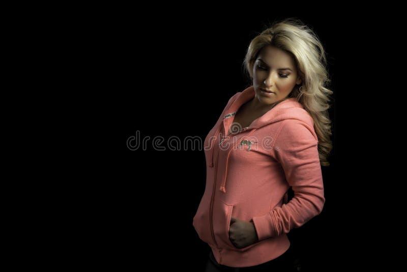 Το ξανθό αθλητικό κορίτσι ρόδινο Hoodie απομόνωσε το μαύρο υπόβαθρο στοκ εικόνες